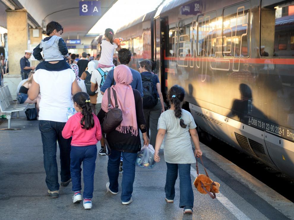 Varios refugiados procedentes de Hungría se suben a un tren con destino a Alemania.