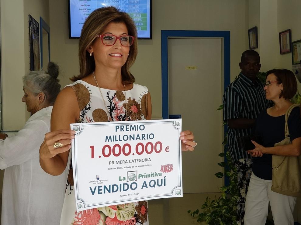 La propietaria de la administración, Andrea Ballesté, muestra el cartel del millonario premio.