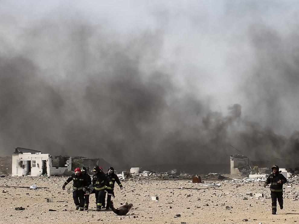 Un grupo de bomberos trabajan sobre el terreno donde ha tenido lugar la explosión.