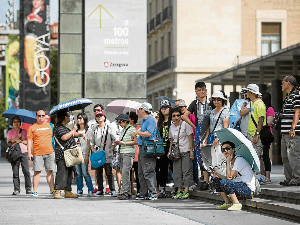 Un nutrido grupo de turistas asiáticos, junto a la oficina de Turismo de la plaza del Pilar.