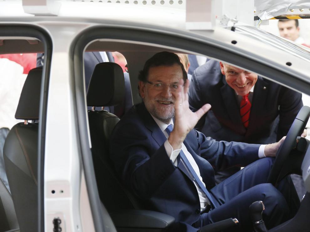 El presidente del Gobierno, Mariano Rajoy, junto al presidente de SEAT, Jürgen Stackmann, saluda desde el interior de un prototipo