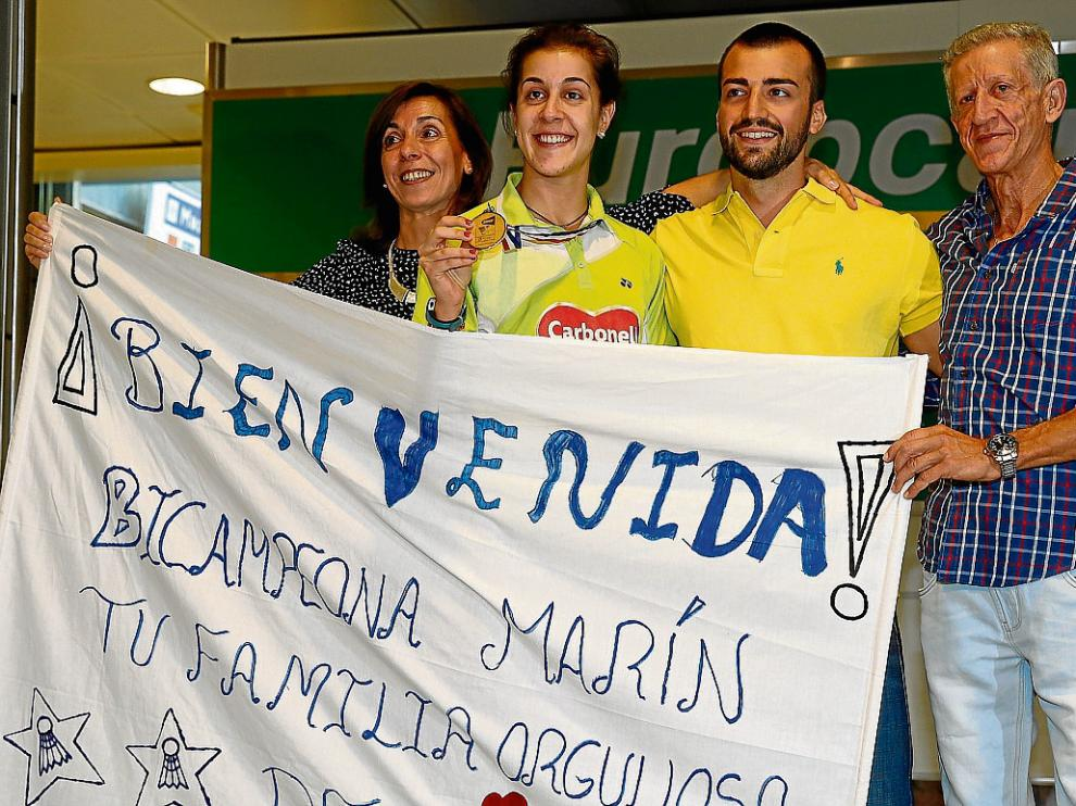 Carolina Marín, recibida ayer por sus padres y su pareja en el aeropuerto de Madrid.