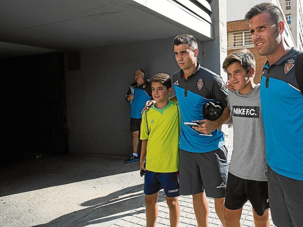 Jaime y Ortuño posan con dos jóvenes aficionados antes de la partida del equipo zaragocista rumbo a Miranda de Ebro.