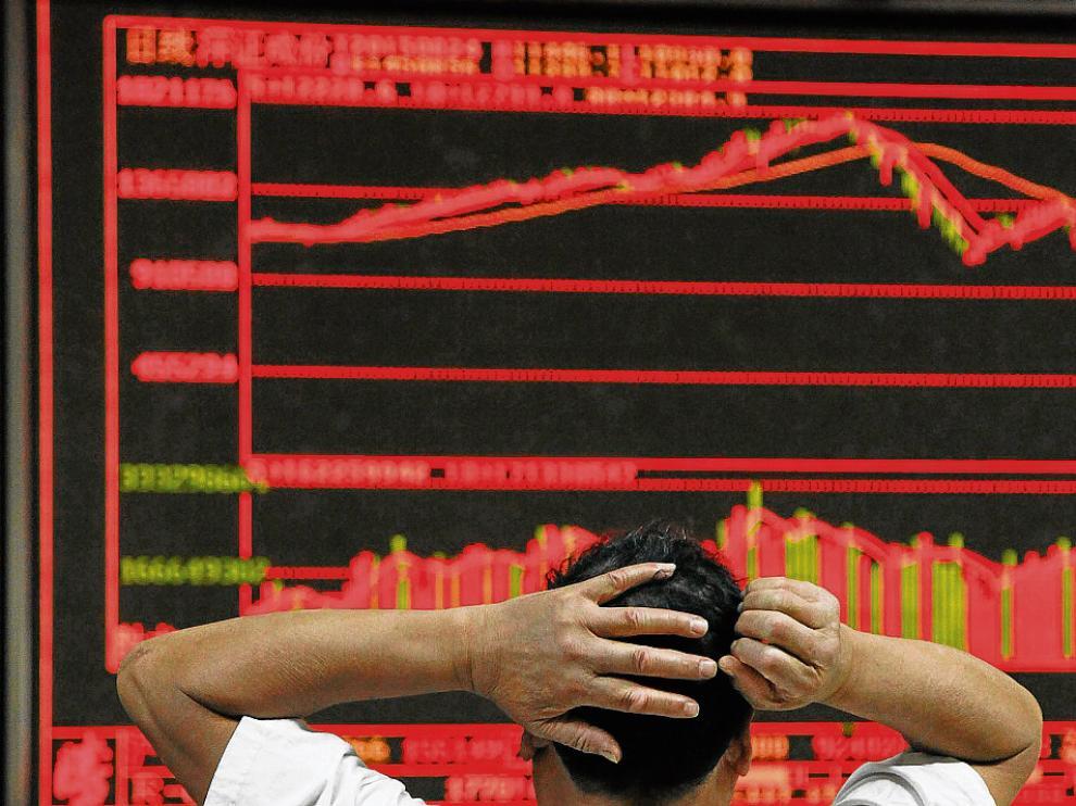 Un inversor se lleva las manos a la cabeza con el desplome de la bolsa ayer en Pekín.