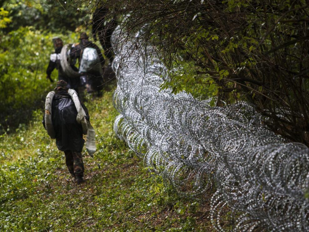 Varios soldados húngaros levantan una alambrada en la frontera con Croacia.