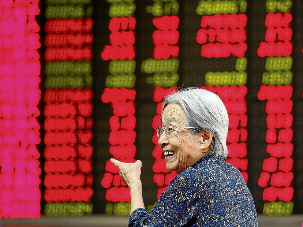Una mujer sonríe al ver las cifras de la recuperación de la bolsa china, en Pekín.