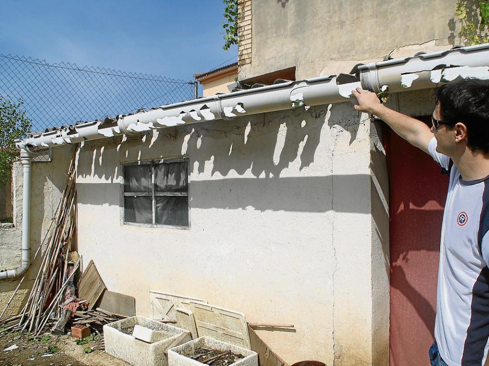 El concejal de Urbanismo y tesorero del Ayuntamiento de Torre del Compte, Miguel Burgués, muestra un canal de agua del tejado de una caseta de  huerta, que quedó destrozado después del inesperado granizo del pasado lunes.