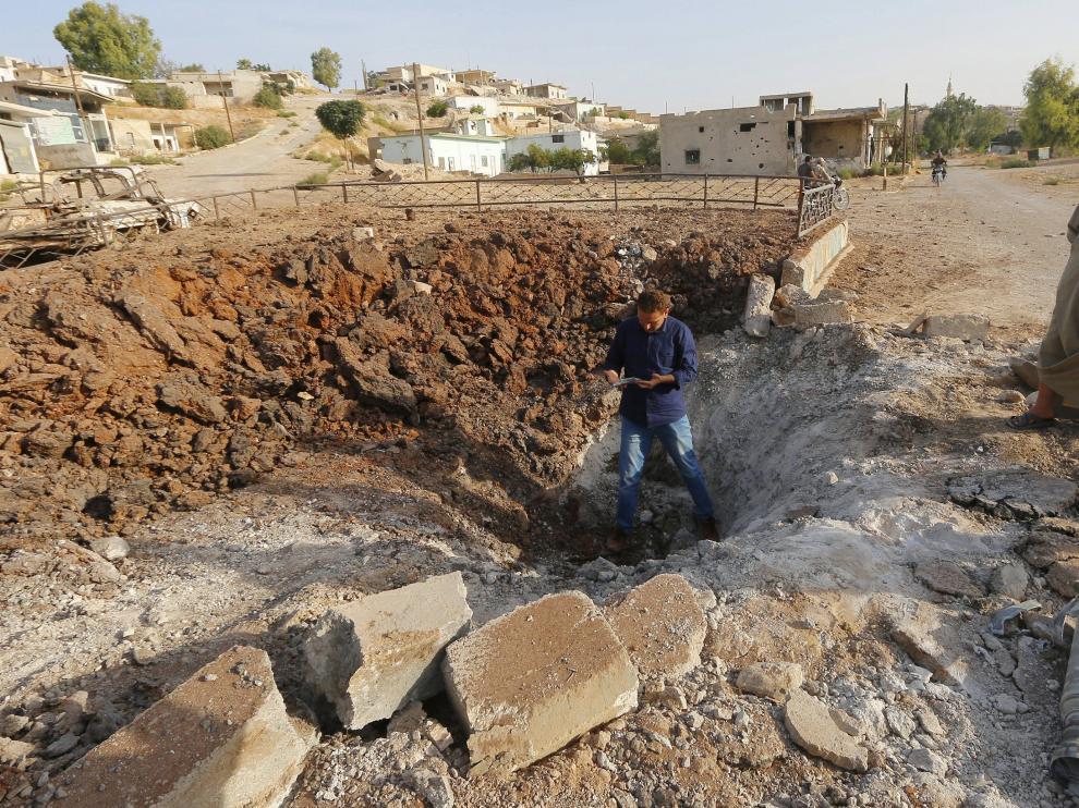 Un hombre de pie sobre un cráter causado según algunos medios por Rusia en Latamneh (Siria).