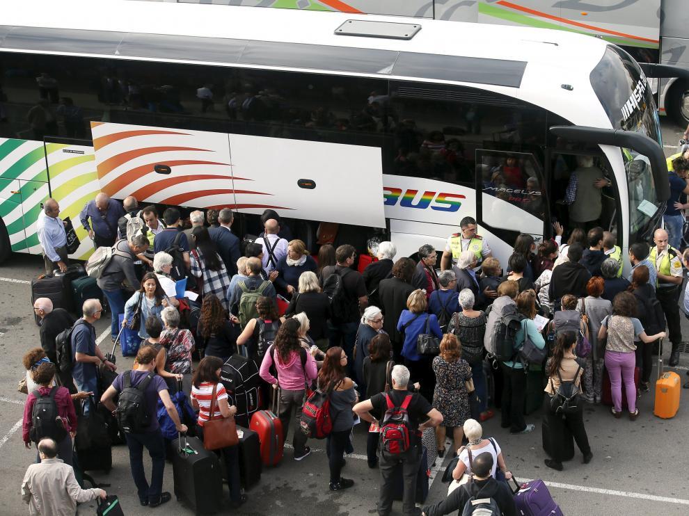 Varios pasajeros toman un bus lanzadera a causa de la suspensión de la línea ferroviaria.