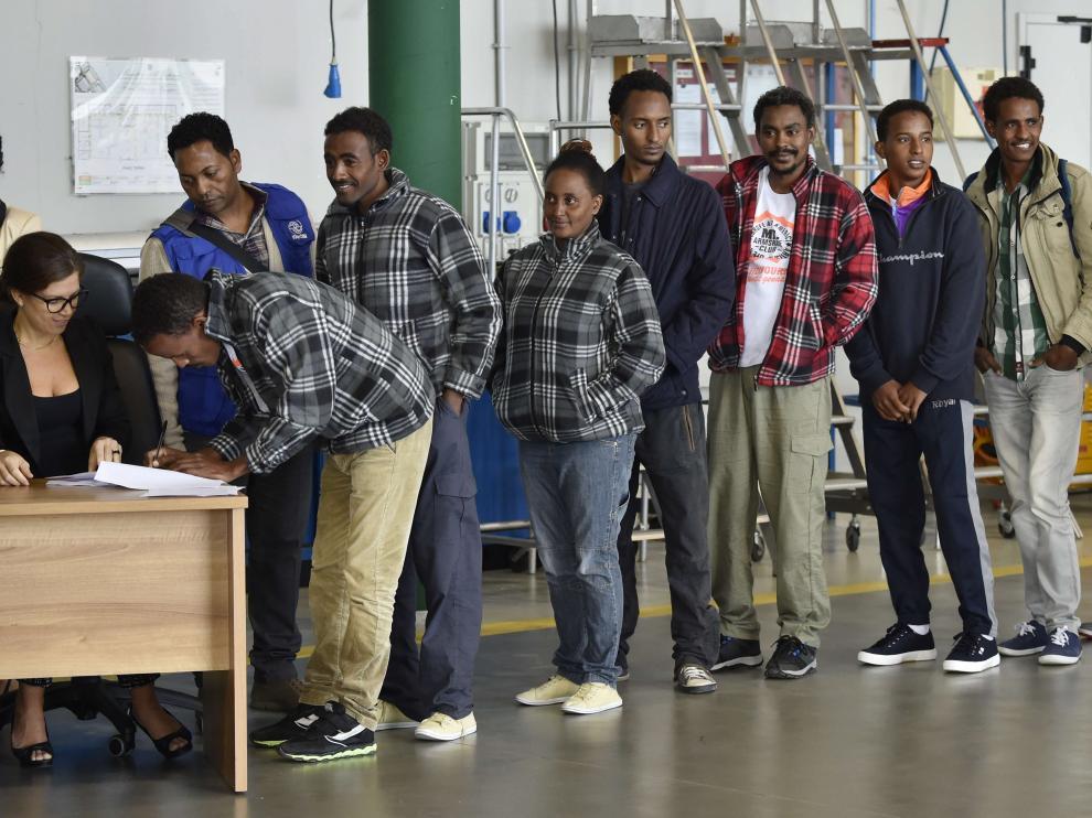 Un grupo de eritreos guardan fila antes de partir de Italia hacia Suecia.