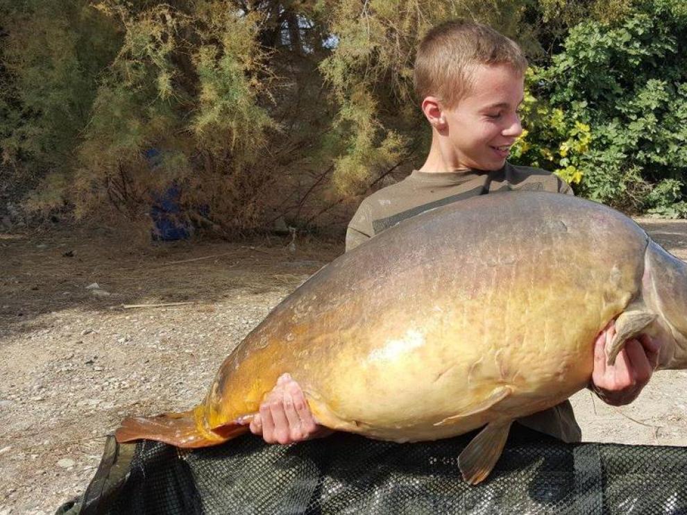 El joven pescador posa con la carpa capturada.