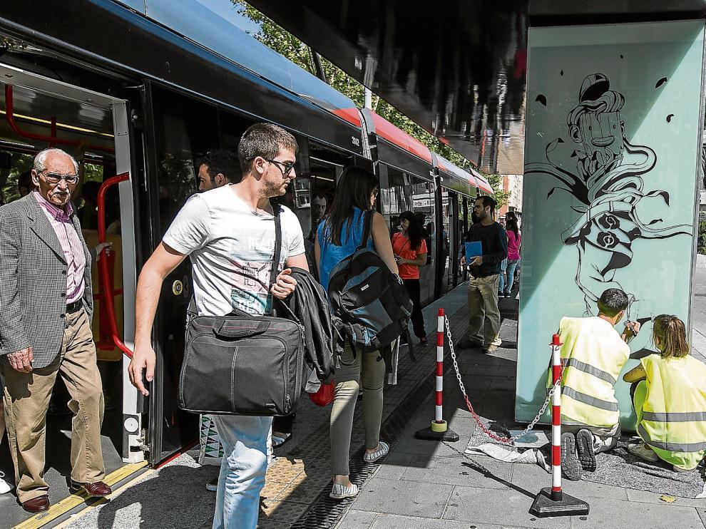 Los artistas de Twee Muizen, Denís Galocha y Cristina Barrientos (de espalda con chaleco) pintan en la plaza de San Francisco.