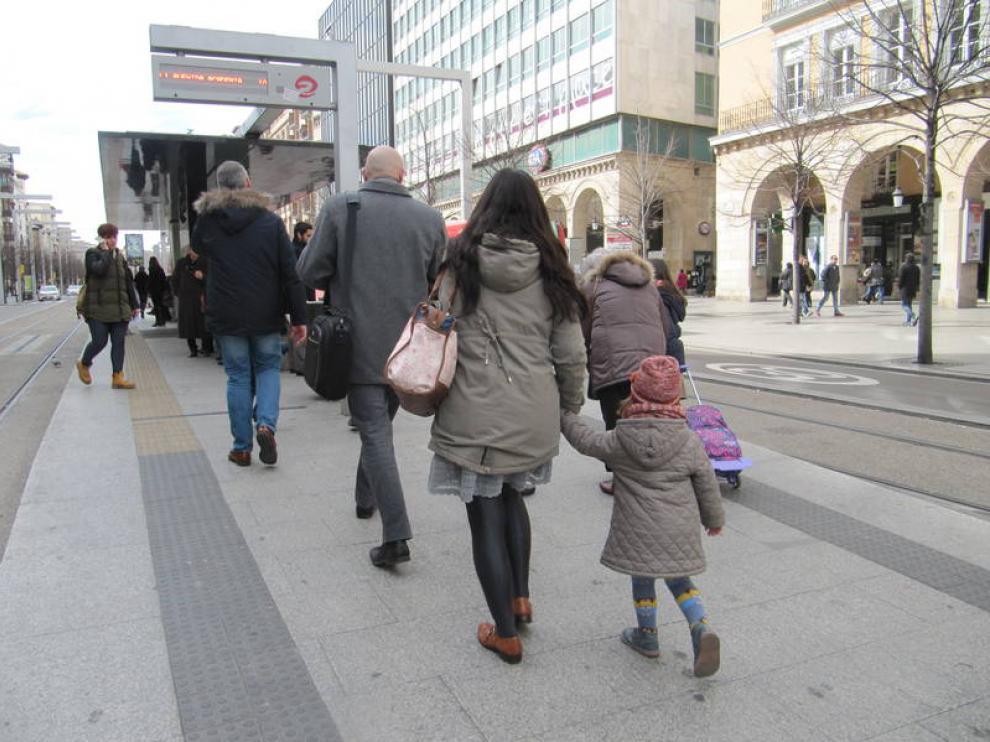 Una madre con su hija en la parada del tranvía de la plaza de España.