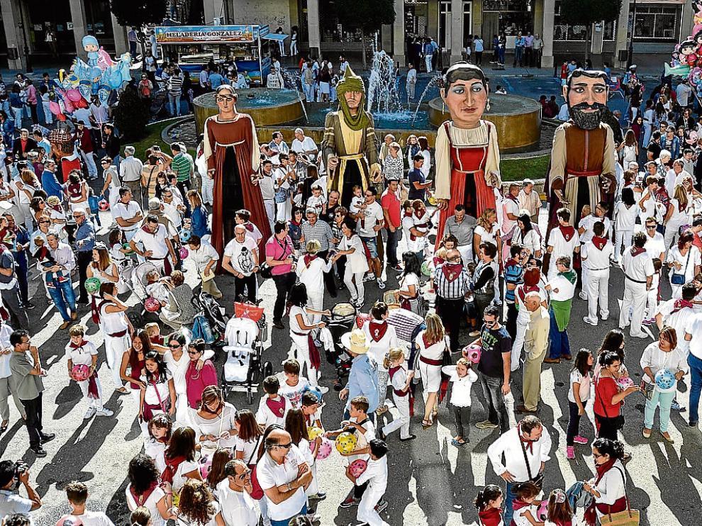 La comparsa de gigantes y cabezudos siguió al chupinazo en el primer día festivo en Tauste.
