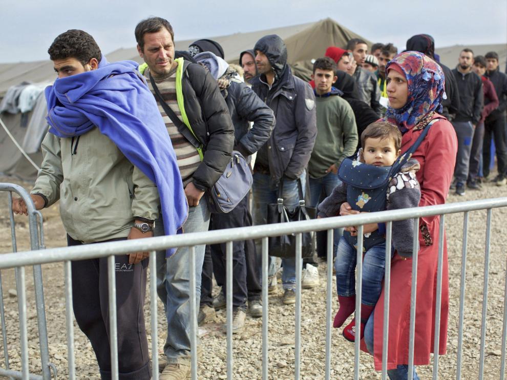 Refugiados hacen fila para entrar a un campamento en la frontera Serbia.