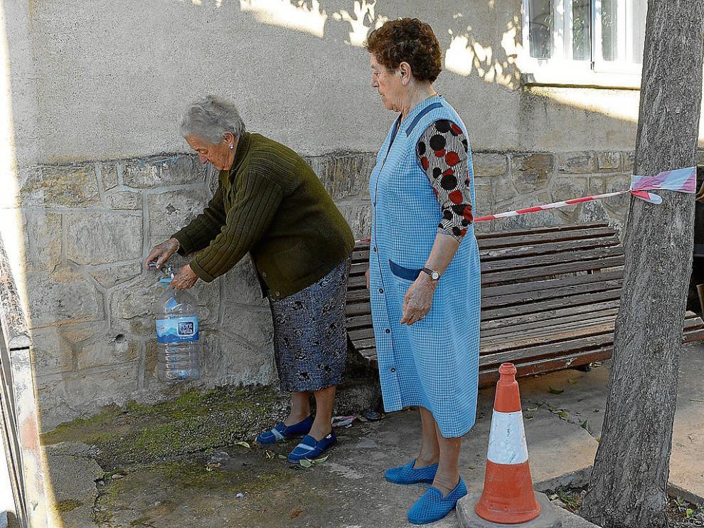 Dos vecinas de Bello llenaban ayer garrafas con agua procedente de la desnitrificadora.