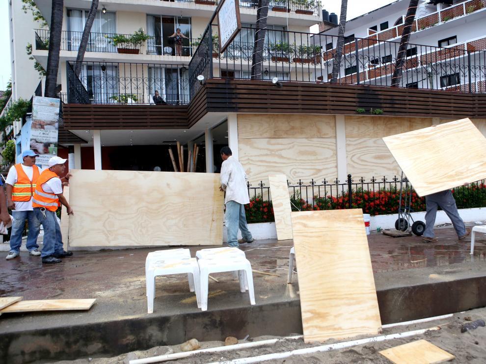 Habitantes de la zona turística de Puerto Vallarta en el estado de Jalisco protegen sus casas y comercios.