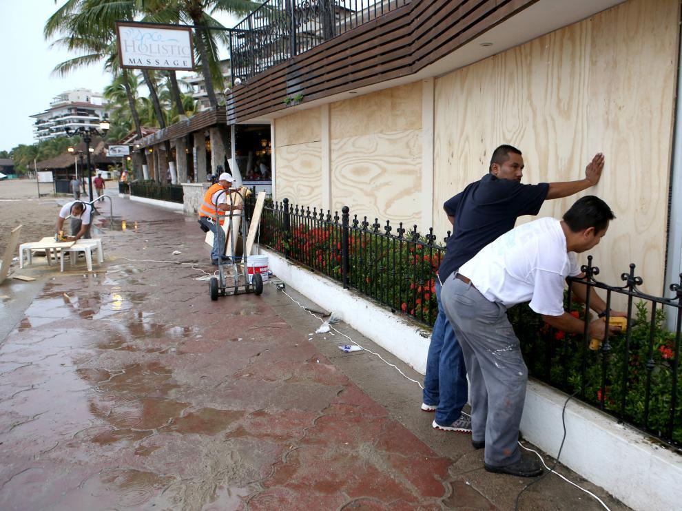 abitantes de la zona turística de Puerto Vallarta en el estado de Jalisco protegen sus casas y comercios.