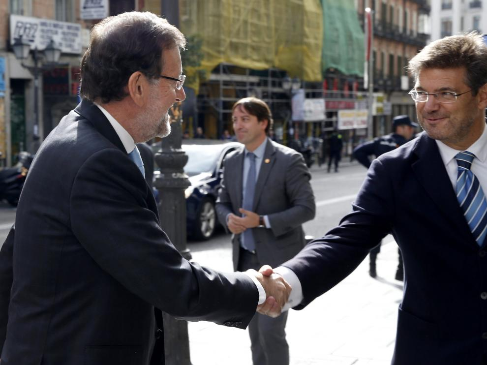 El presidente del Gobierno, Mariano Rajoy y el ministro de Justicia, Rafael Catalá, se saludan antes de la inauguración de la Oficina de Recuperación y Gestión de Activos.