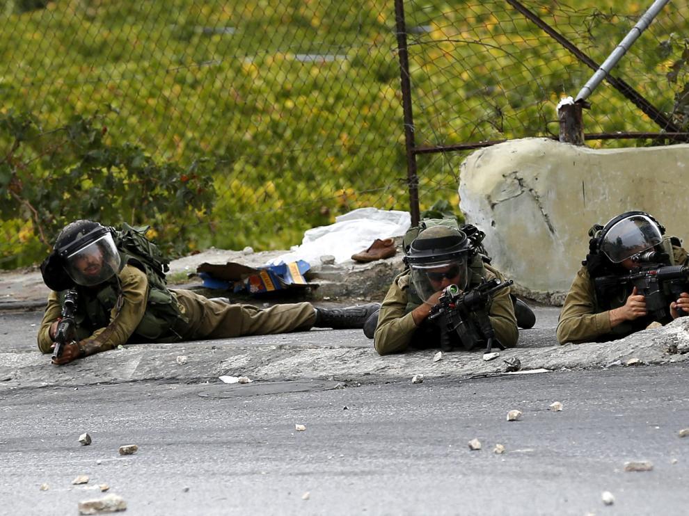 Soldados del ejército israelí toman posiciones durante un enfrentamiento con manifestantes palestinos en la ciudad cisjordana de Hebrón,