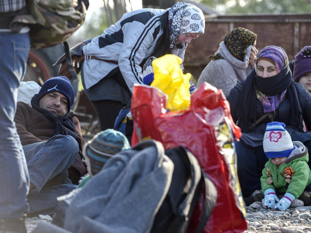 Refugiados esperan obtener permiso para entrar en el centro de registro tras cruzar la frontera entre Grecia y Macedonia.