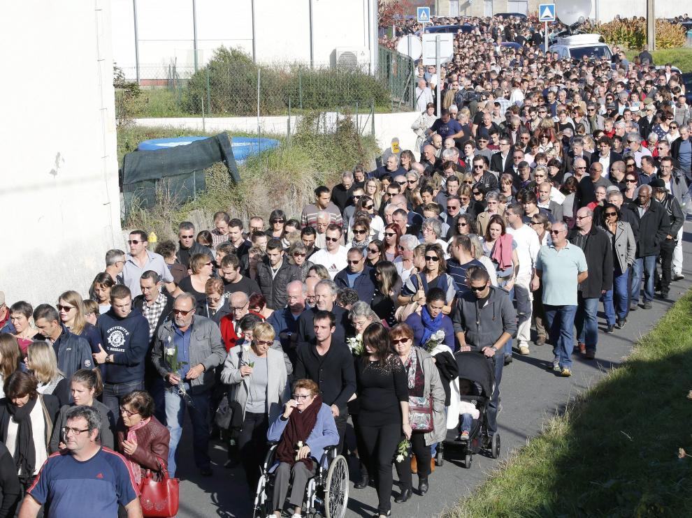 Ciudadanos inician una marcha silenciosa en honor a las víctimas del accidente de autobús.