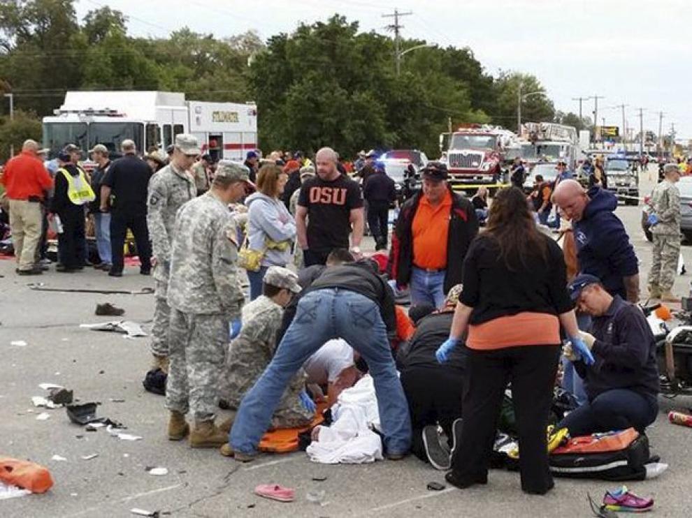 Los asistentes tratan de atender a las víctimas de la embestida en el desfile de la Universidad de Oklahoma.