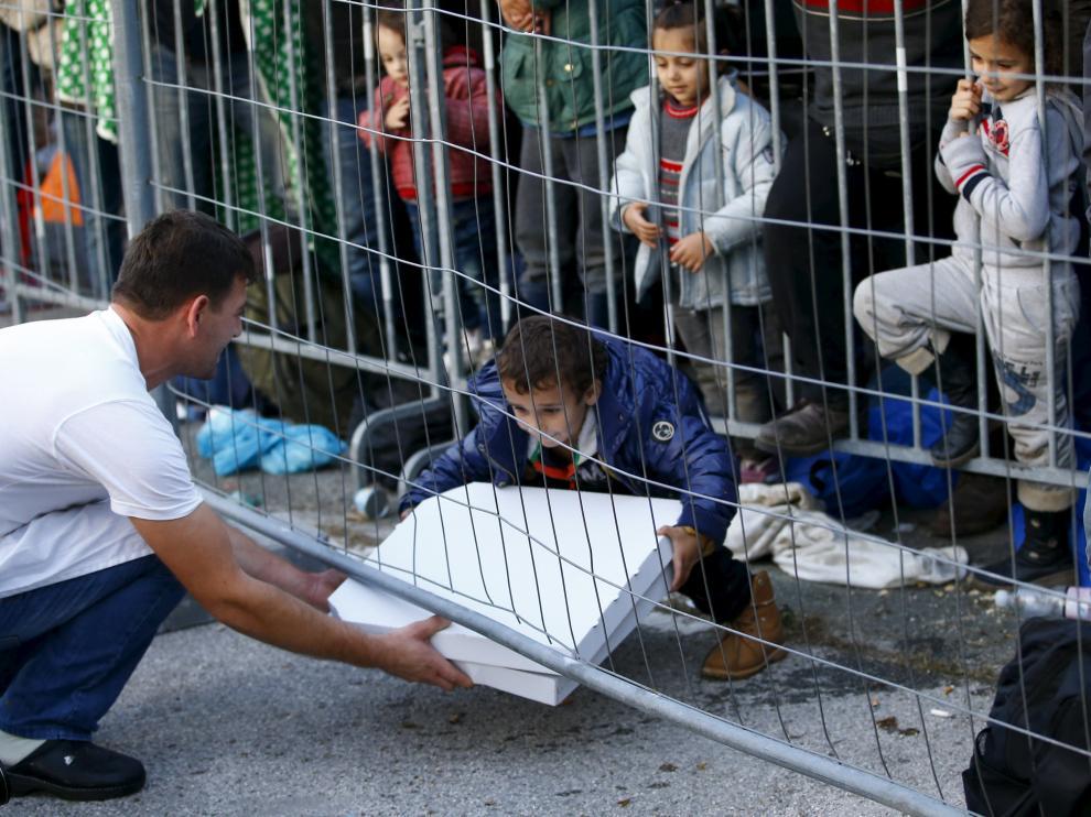 Un camarero entrega una pizza a un grupo de niños en la frontera de Eslovenia.