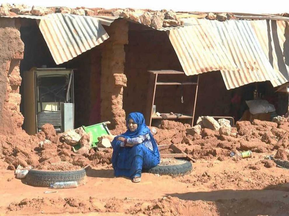 Un mujer sentada junto a los escombros provocados por las lluvias en un campo saharau