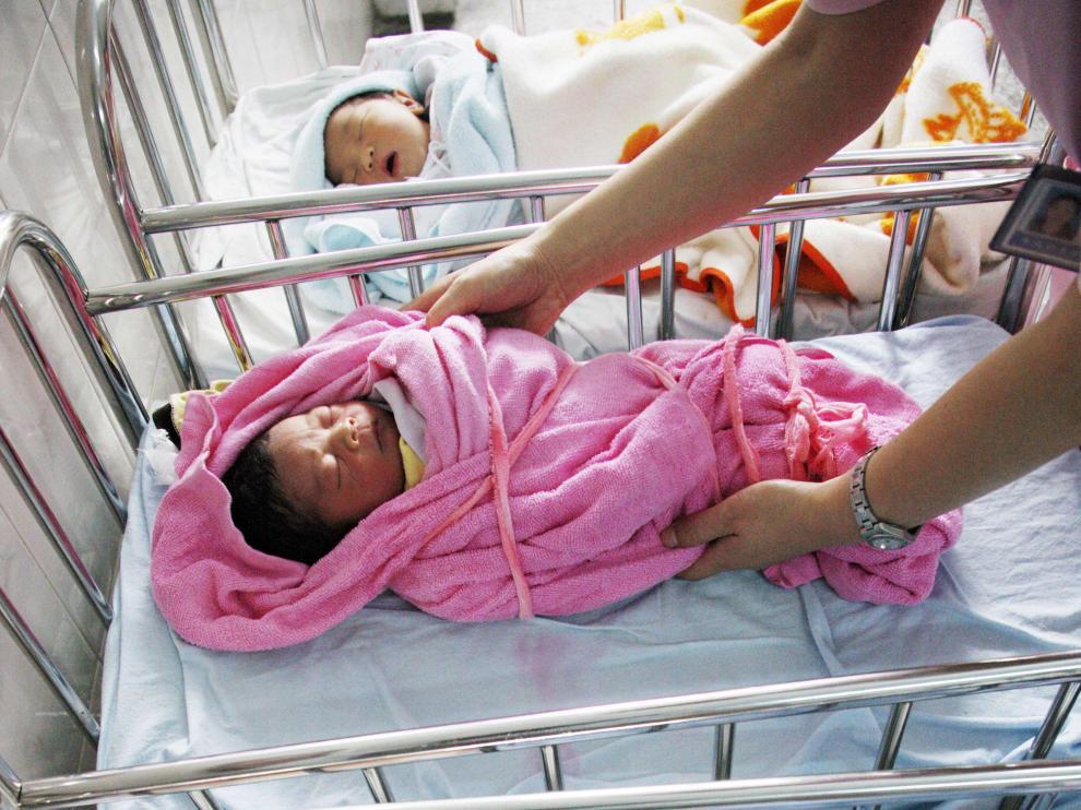 Una enfermera china atiende a dos bebés.