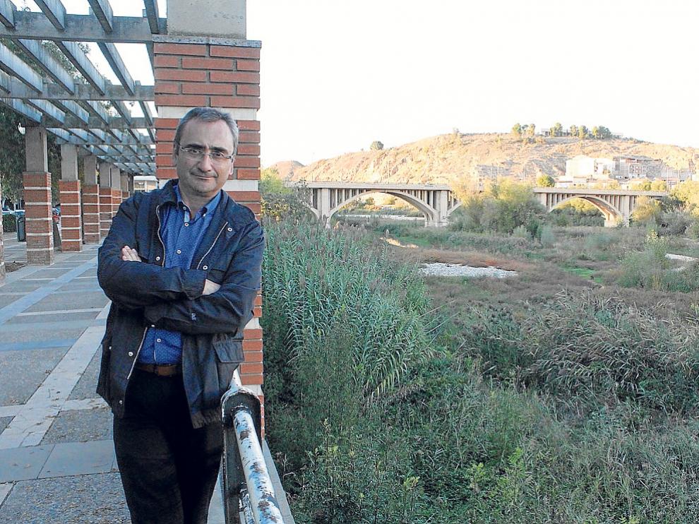El alcalde de Fraga, Miguel Luis Lapeña, junto al cauce del Cinca para el que pide medidas.
