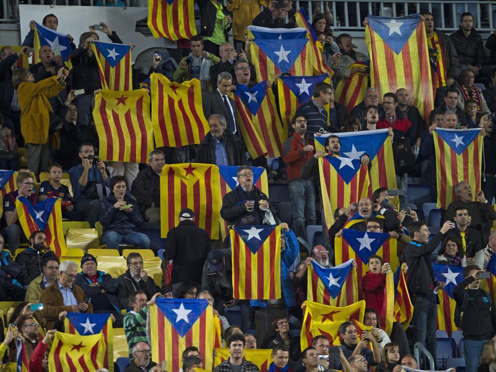 Decenas de voluntarios reparten esteladas a las puertas del Camp Nou