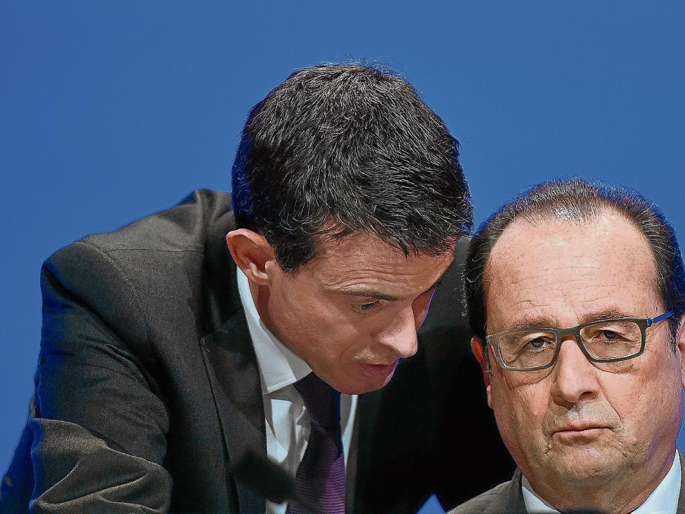 François Hollande escucha atentamente al primer ministro francés, Manuel Valls.