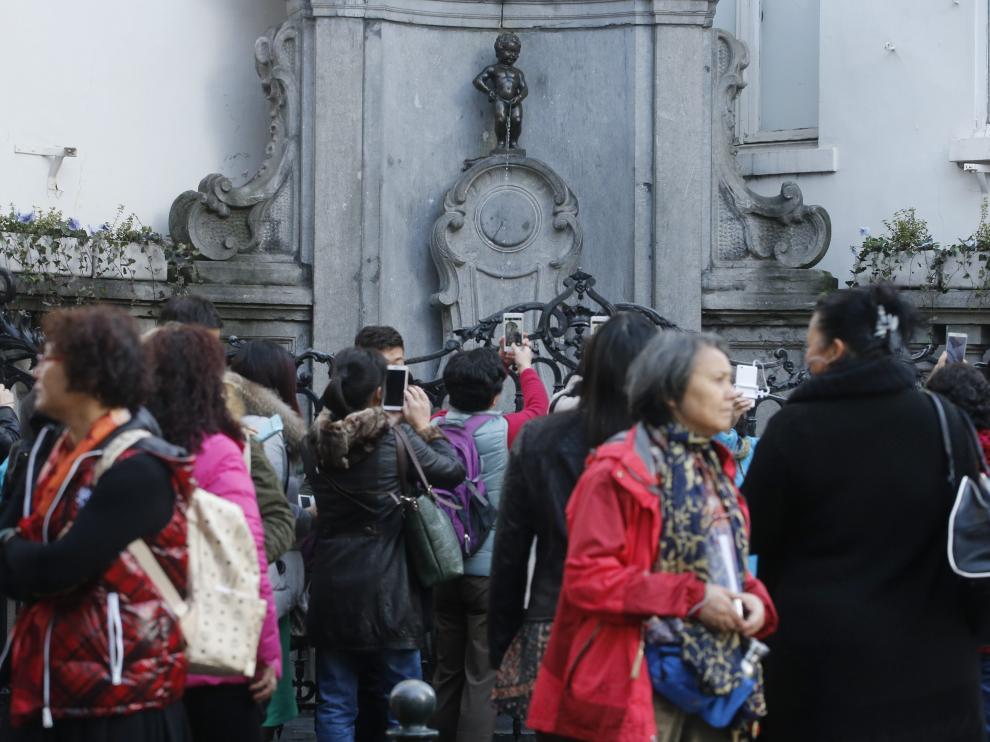 Varios turistas fotografían al Manekken Pis.