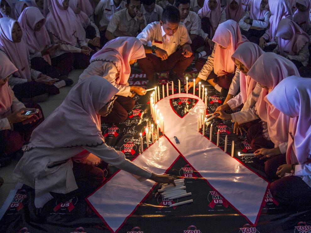 Estudiantes indonesios encienden velas durante un acto conmemorativo del Día Mundial de la lucha contra el sida.