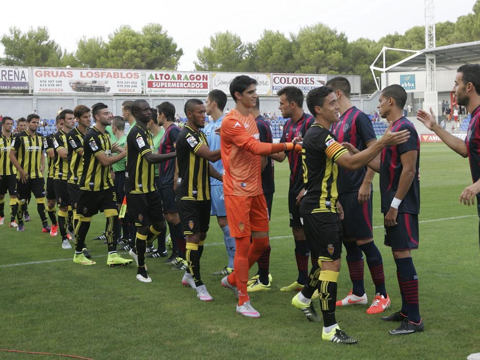 Los jugadores del Real Zaragoza y el Huesca se saludan, en el partido de pretemporada