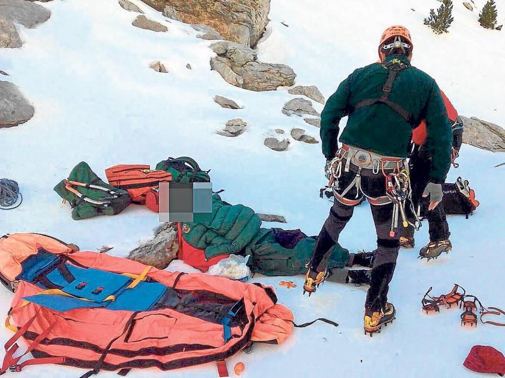 El montañero herido, tendido en el suelo, es atendido por un médico y un guardia de rescate.