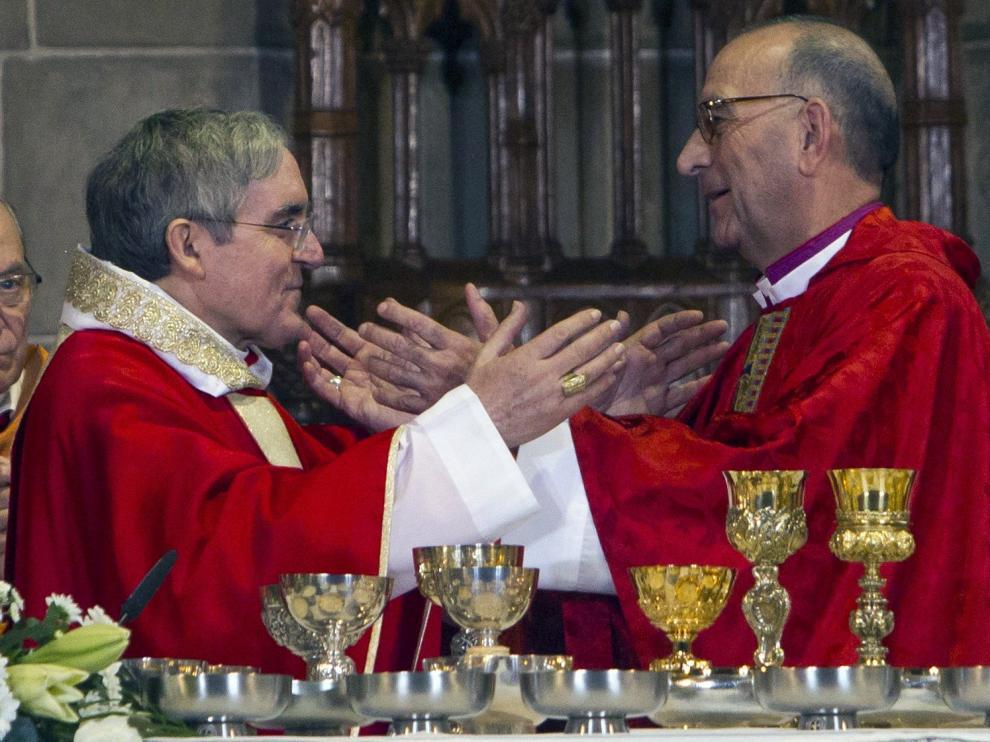 El turolense Juan José Omella (derecha) recibe el testigo al frente del Arzobispado de Barcelona de Lluis María Sistach, este sábado en la catedral de Barcelona.