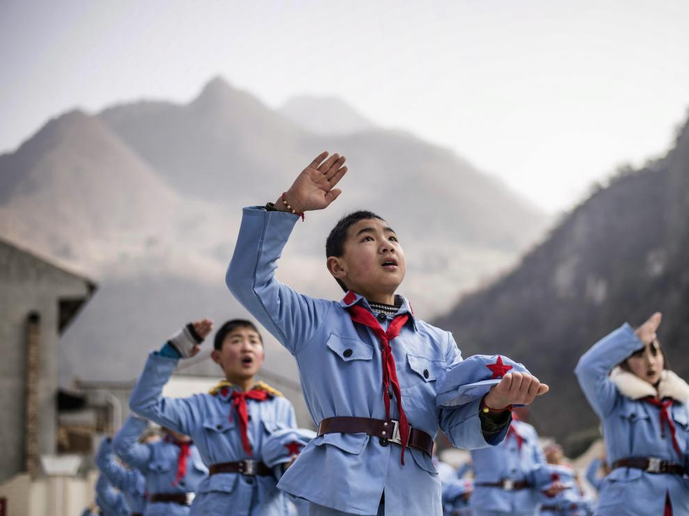 Un niño uniformado canta tras izar la bandera nacional en la escuela de primaria del Ejército Rojo de Beichuan, en la provincia de Sichuan, al suroeste de China. Fotografía tomada el 21 de enero de 2015