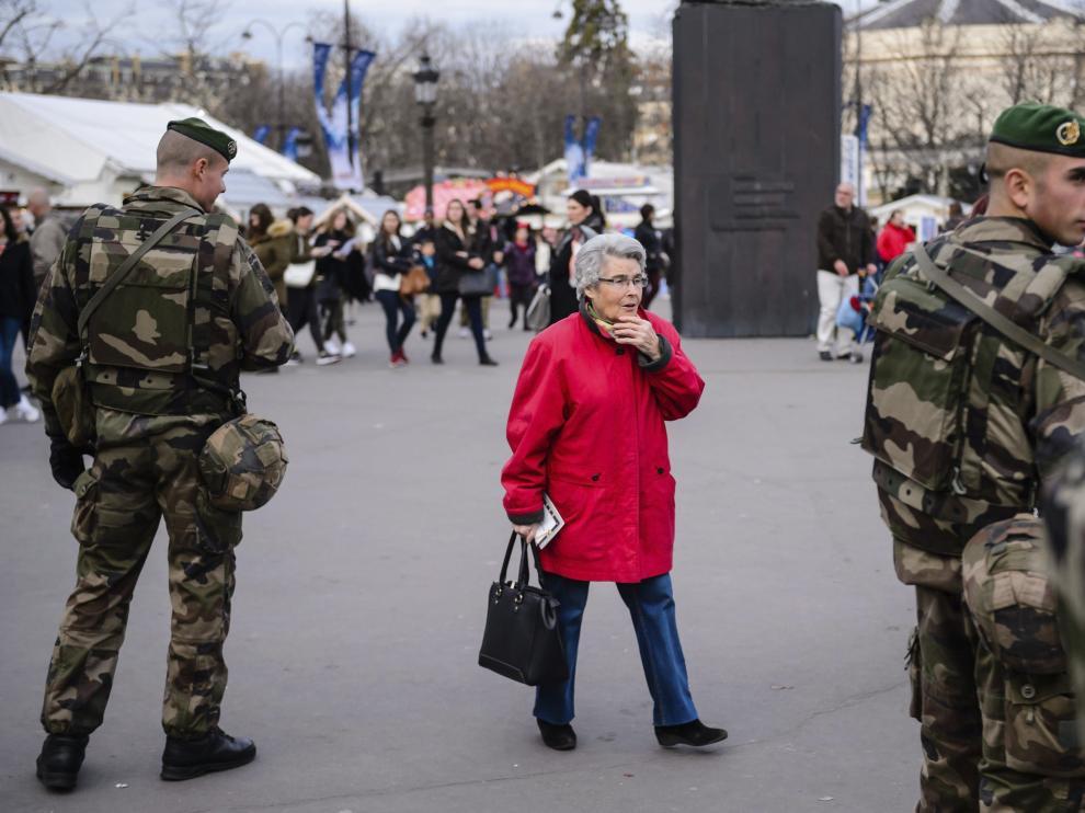 Una mujer camina junto a dos soldados franceses.