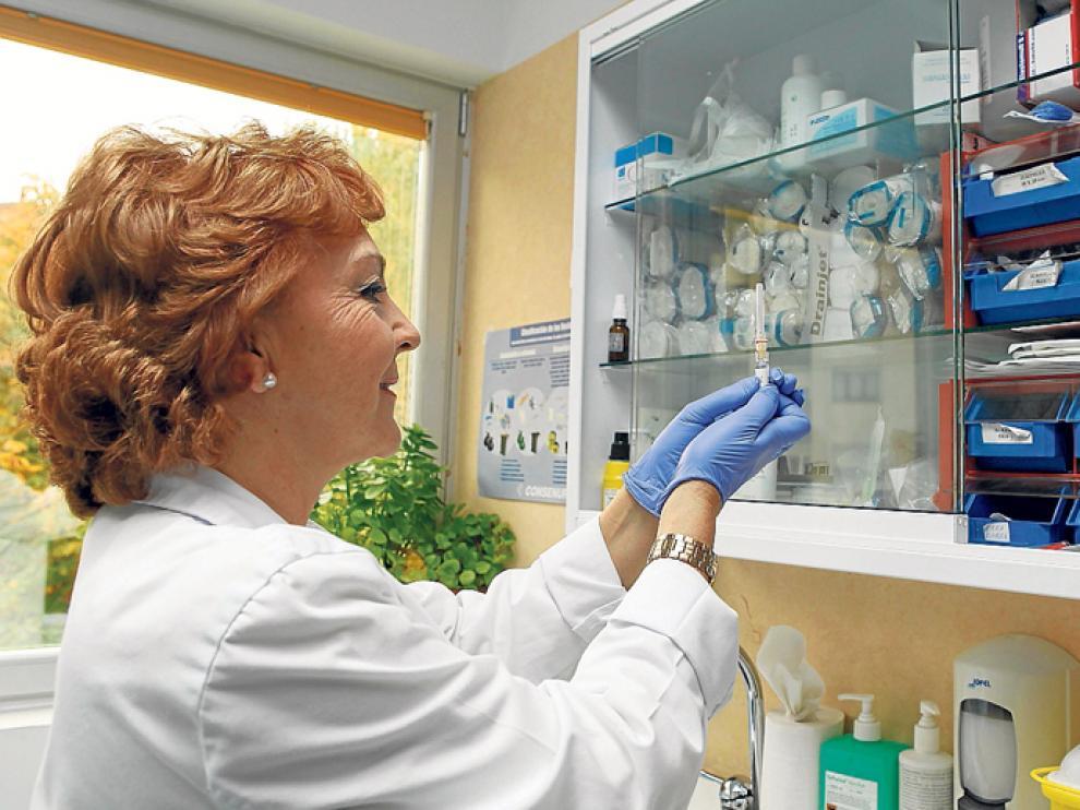 Una profesional sanitaria prepara una dosis para vacunar a un paciente.