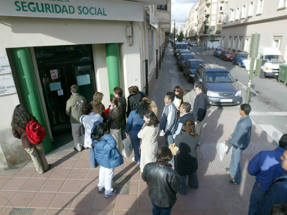 Unos ciudadanos guardan fila ante una oficina de la Seguridad Social.