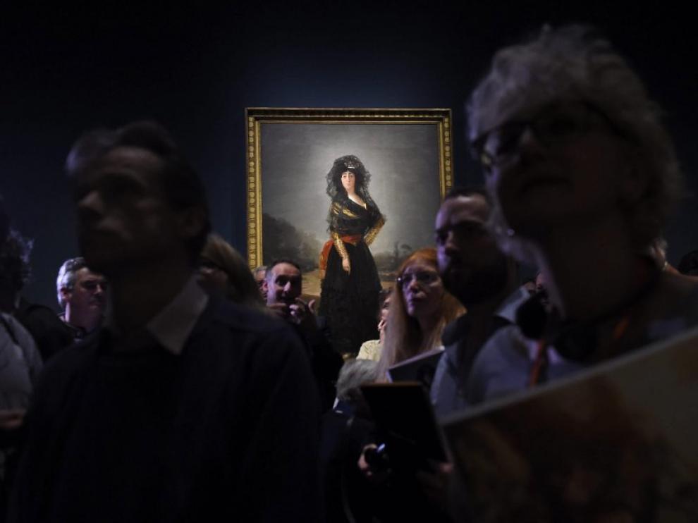 Visitantes de la exposición de retratos de Goya en la National Gallery de Londres, con el cuadro de la Duquesa de Alba de luto al fondo.