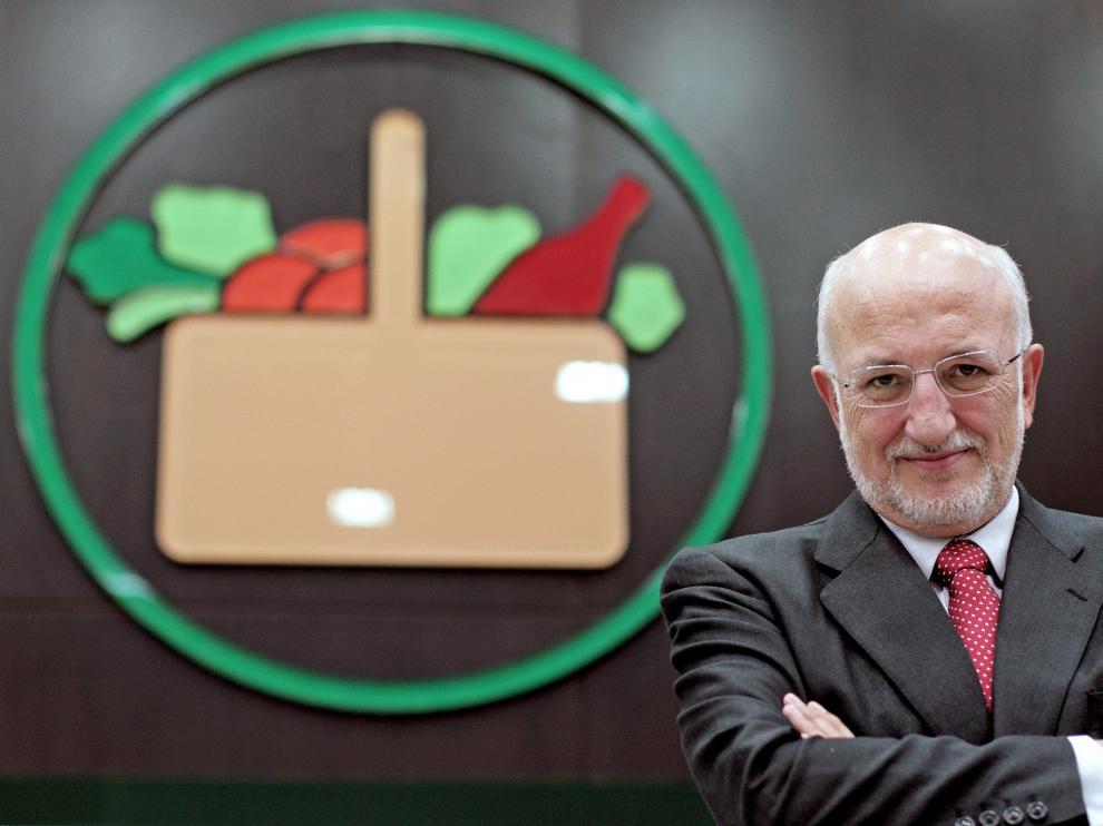 El presidente de Mercadona, Juan Roig, posa junto al logo del supermercado