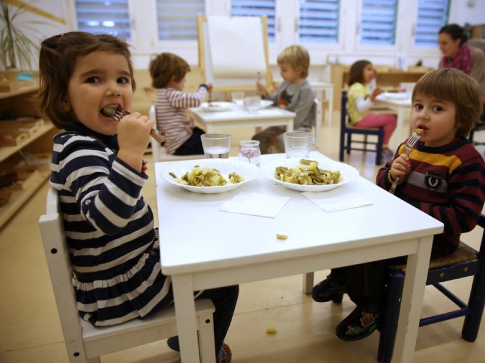 Los niños comen judía verde con patata y salteado de hamburguesa de espelta.