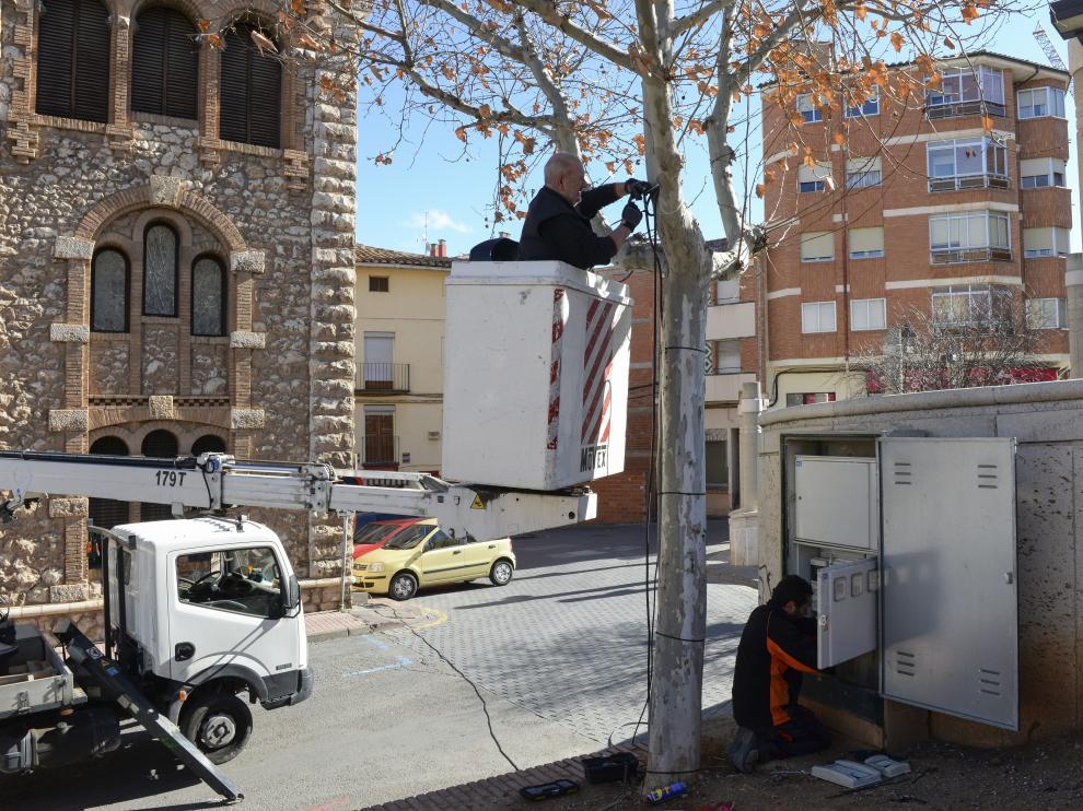 Unos operarios ultiman las instalaciones eléctricas en las zonas de las jaimas.