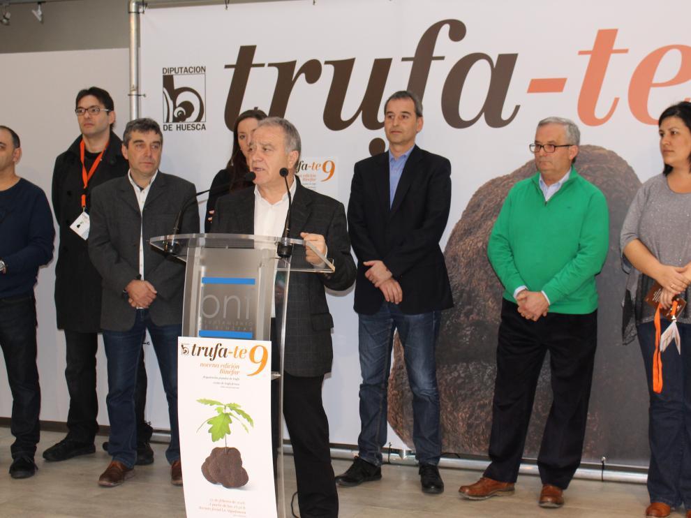 El presidente de la DPH, Miguel Gracia, rodeado por el alcalde de Binéfar, a su espalda, Alfonso Adán, y por los cocineros del certamen.