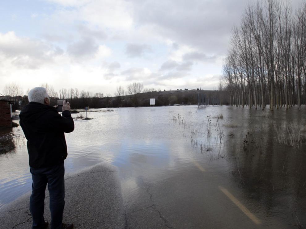 Un hombre fotografía el inusual e inundado panorama de las cercanías del río Duero en Garray.