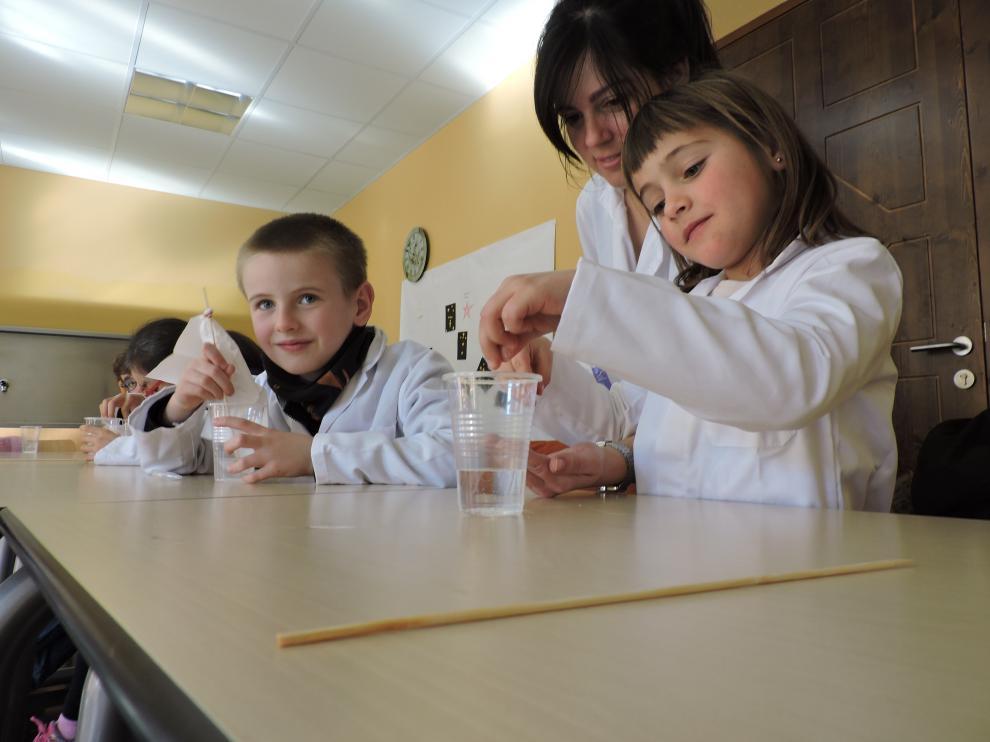 La monitora Ana Abás, con dos alumnos del taller de ciencia de Ibercaja Villahermosa durante la Semana Blanca.