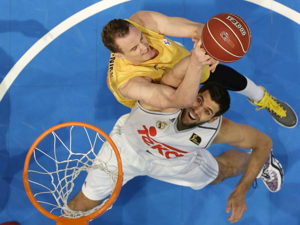 Dos jugadores compiten por el balón en un partido de baloncesto.